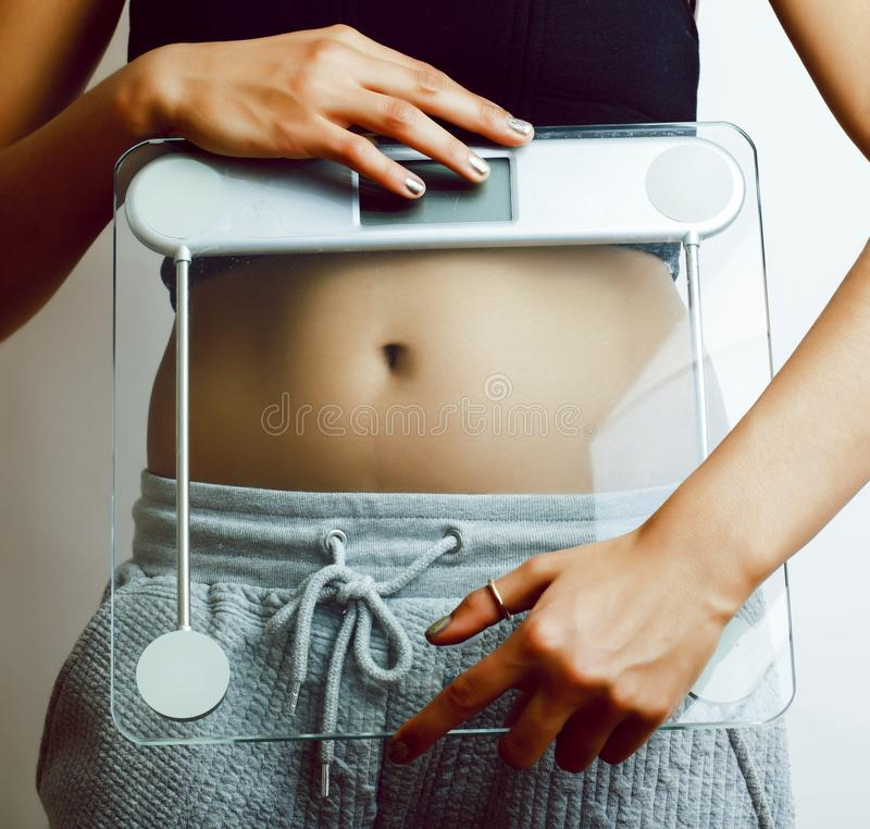 Στενός επάνω μέσης γυναικών στο άσπρο ζύγισμα -ζυγίζω-machin εκμετάλλευσης υποβάθρου στοκ εικόνες