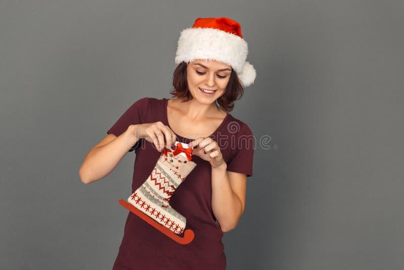 στενός κόκκινος χρόνος Χριστουγέννων ανασκόπησης επάνω Η νέα γυναίκα στο καπέλο santa απομόνωσε στην γκρίζα τοποθέτηση παρούσα στ στοκ εικόνα με δικαίωμα ελεύθερης χρήσης