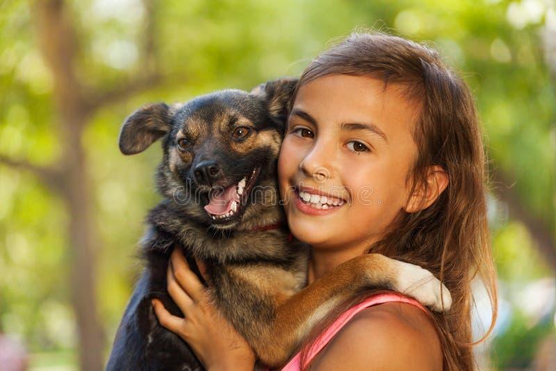Στενό πορτρέτο έφηβη στο αγκάλιασμα λίγου σκυλιού στοκ εικόνα με δικαίωμα ελεύθερης χρήσης