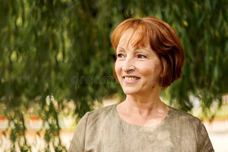 Στενό πορτρέτο μιας όμορφης μέσης ηλικίας γυναίκας που κοιτάζει μακριά με ένα υπόβαθρο του πράσινου φυλλώματος στοκ φωτογραφία