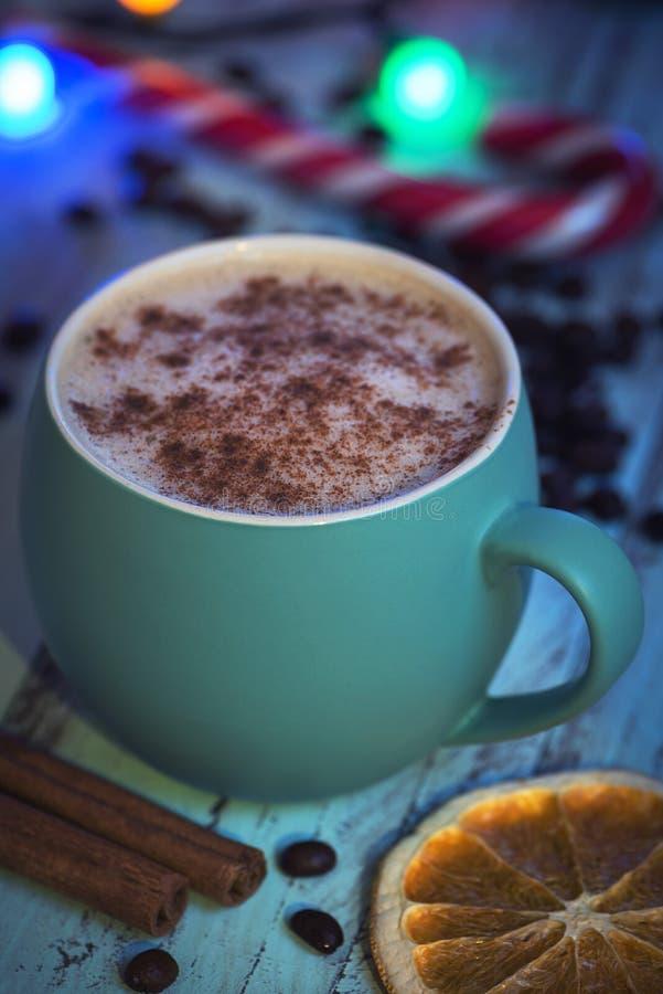 Στενό cappuccino άποψης στην πράσινη κούπα με τη διακόσμηση και τις καραμέλες Χριστουγέννων Πορτοκάλι και καραμέλα στοκ εικόνα με δικαίωμα ελεύθερης χρήσης