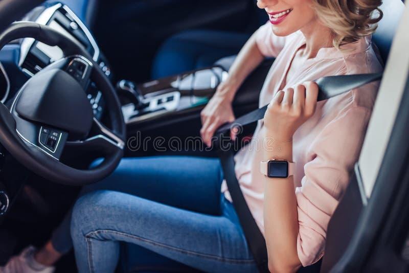 Στερεώνοντας ζώνη ασφάλειας γυναικών στο αυτοκίνητο στοκ εικόνα