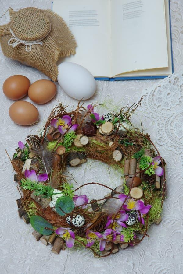 Στεφάνι Πάσχας με τα ιώδη λουλούδια στο υπόβαθρο του βιβλίου και των αυγών στοκ εικόνα με δικαίωμα ελεύθερης χρήσης