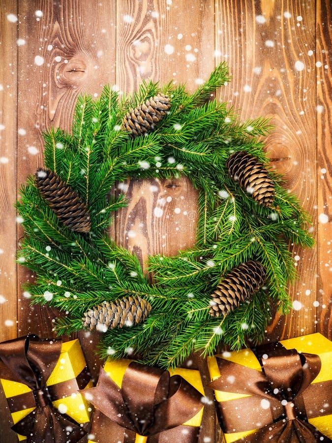 Στεφάνι στον ξύλινο πίνακα δώρο κιβωτίων που τυλίγεται νέο έτος έννοιας Χριστου&gamm στοκ εικόνα