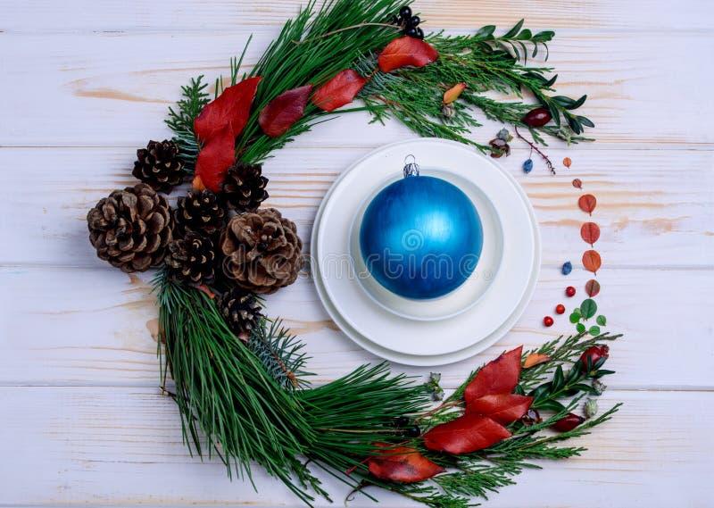 Στεφάνι του ιουνιπέρου και των λουλουδιών με τα άσπρα πιάτα και Χριστούγεννα στοκ φωτογραφία με δικαίωμα ελεύθερης χρήσης