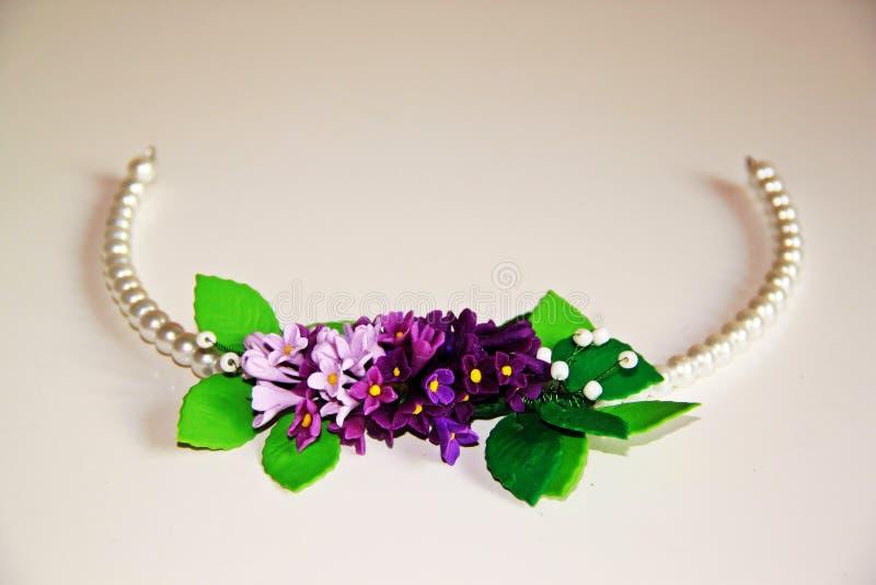 Στεφάνι των άσπρων και πορφυρών λουλουδιών με τα μαργαριτάρια για το κεφάλι στοκ εικόνα με δικαίωμα ελεύθερης χρήσης