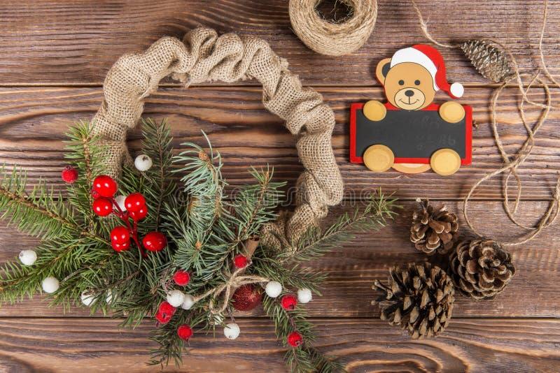 στεφάνι Χειμερινό πλαίσιο Χριστουγέννων στο σκοτεινό ξύλινο υπόβαθρο Κόκκινα στοιχεία, halk πίνακας Ñ  με το santa στοκ εικόνες με δικαίωμα ελεύθερης χρήσης
