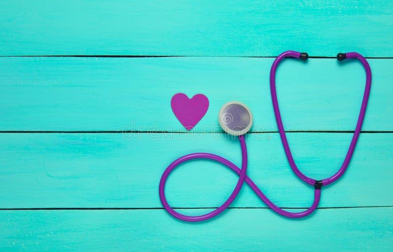 Στηθοσκόπιο και καρδιά σε έναν μπλε ξύλινο πίνακα στοκ εικόνα με δικαίωμα ελεύθερης χρήσης