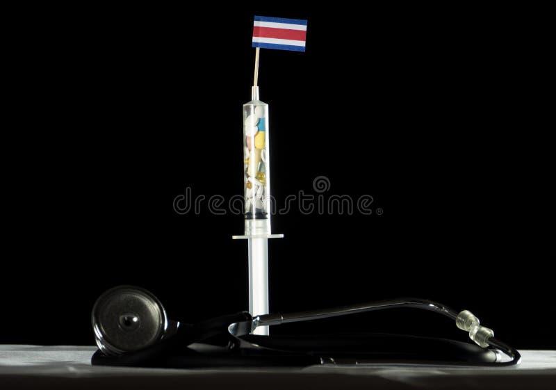 Στηθοσκόπιο και σύριγγα που γεμίζουν με τα φάρμακα που εγχέουν την από την Κόστα Ρίκα σημαία σε ένα μαύρο υπόβαθρο στοκ εικόνες