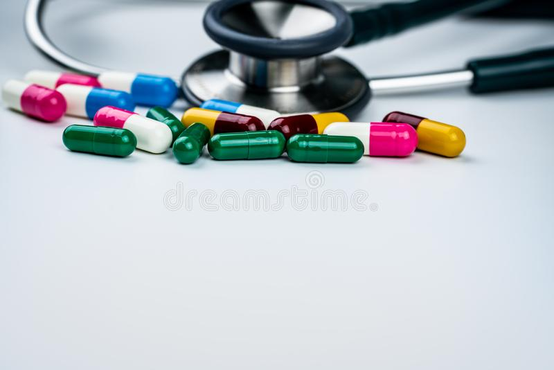 Στηθοσκόπιο με το σωρό των αντιβιοτικών χαπιών καψών στο άσπρο υπόβαθρο Αντιμικροβιακή αντίσταση και κατάχρηση φαρμάκων ιατρικός στοκ εικόνες με δικαίωμα ελεύθερης χρήσης