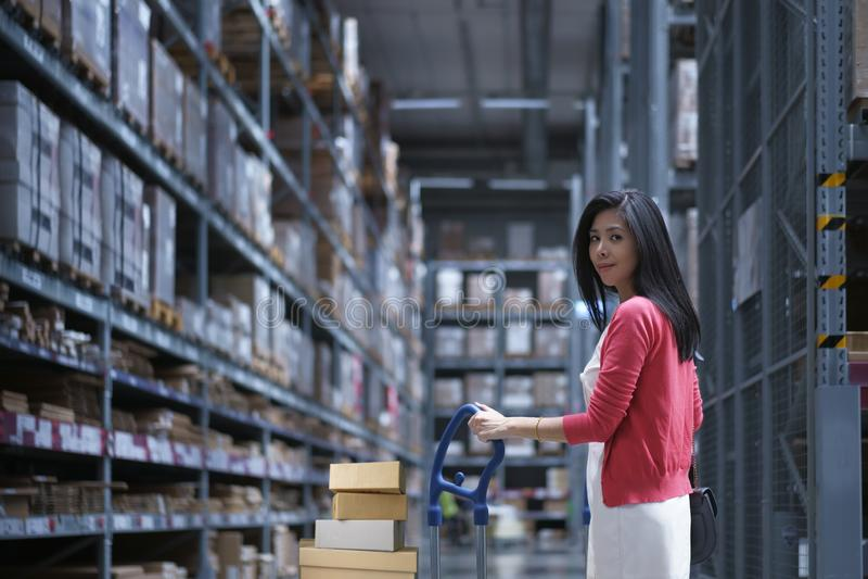 Στην αποθήκευση αποθηκών εμπορευμάτων, φέρνοντας κάρρο καταστημάτων γυναικών της Ασίας για τις αγορές και επίλεκτος για να αγοράσ στοκ φωτογραφία