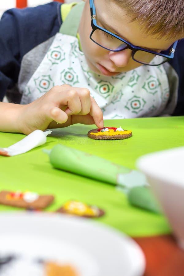 Στην εργασία του προσώπου του αγοριού με τα γυαλιά και μια ποδιά κουζινών, η οποία διακοσμεί τα μπισκότα χρησιμοποιώντας την τήξη στοκ φωτογραφία