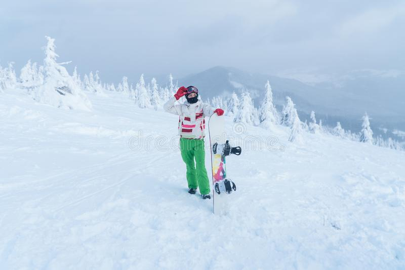 Στην κορυφή του σνόουμπορντ χειμερινών βουνών βουνών Σνόουμπορντ εκμετάλλευσης γυναικών στοκ φωτογραφίες