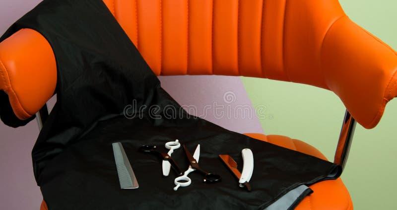 Στην ομορφιά το σαλόνι στην πορτοκαλιά καρέκλα βρίσκεται εργαλεία για τα κουρέματα, ψαλίδι, και για το ξύρισμα της λεπίδας ξυραφι στοκ εικόνες