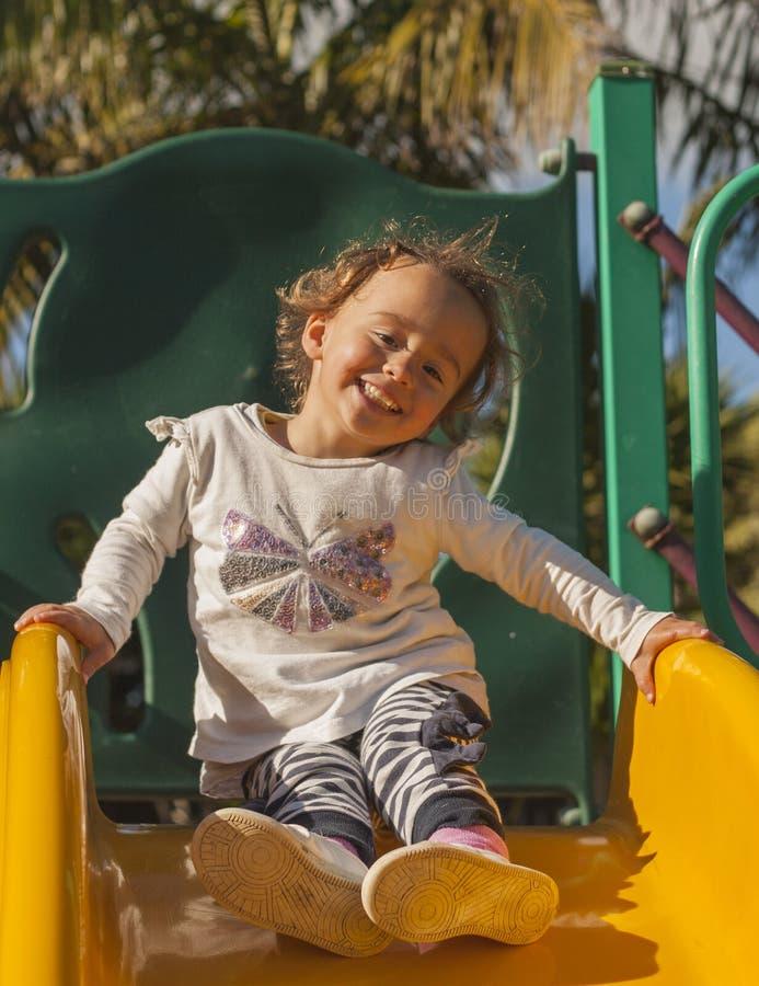 Στην παιδική χαρά, ένα μικρό κορίτσι κυλά ευτυχώς κάτω το λόφο στοκ εικόνες