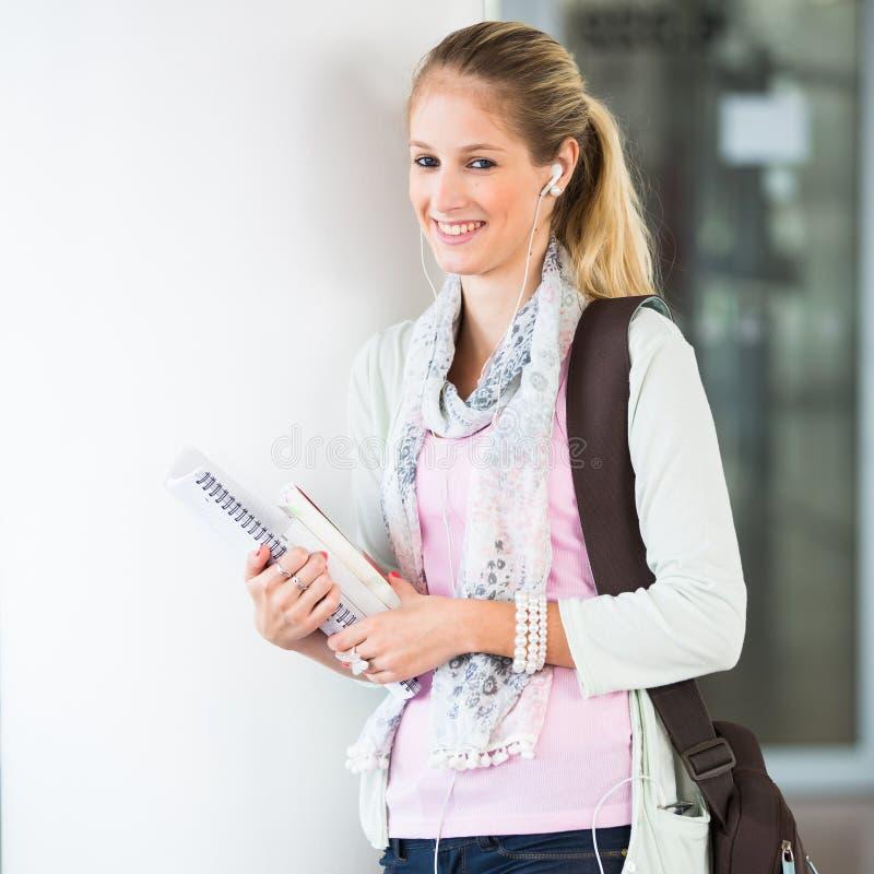 Στην πανεπιστημιούπολη - όμορφη, γυναίκα σπουδαστής με τα βιβλία στοκ εικόνες