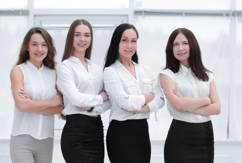 Στην πλήρη αύξηση πορτρέτο της επιτυχούς επιχειρησιακής ομάδας που στέκεται στην αρχή στοκ φωτογραφία