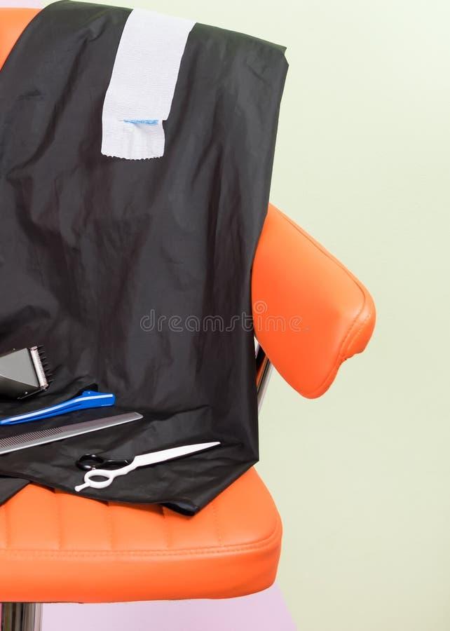 Στην πορτοκαλιά καρέκλα είναι συσκευές για την τρίχα στοκ φωτογραφία