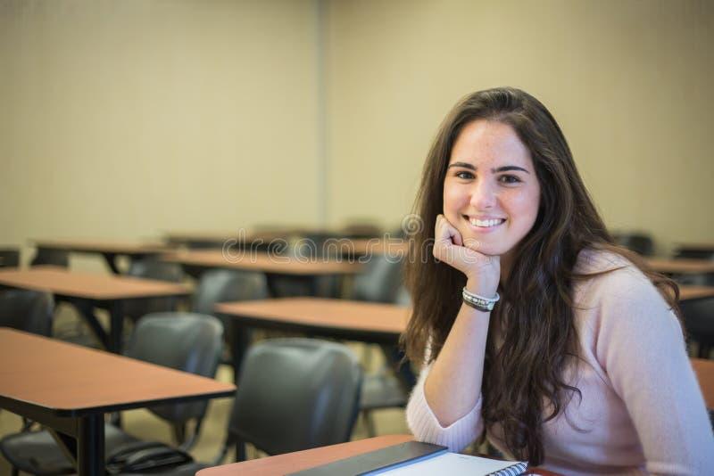 Στην τάξη - αρκετά γυναίκα σπουδαστής με τα βιβλία που λειτουργούν στο α στοκ εικόνες