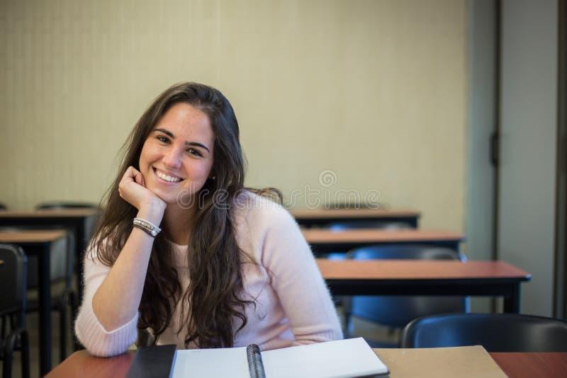 Στην τάξη - αρκετά γυναίκα σπουδαστής με τα βιβλία που λειτουργούν στο α στοκ φωτογραφία