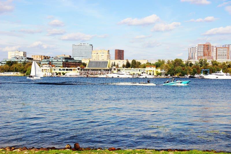 στην όχθη του ποταμού Ιστιοπλοΐα, μοτοσικλέτα, γιοτ και πλοία στον ποταμό της μεγάλης πόλης θαλάσσιες μεταφορές, στοκ φωτογραφία