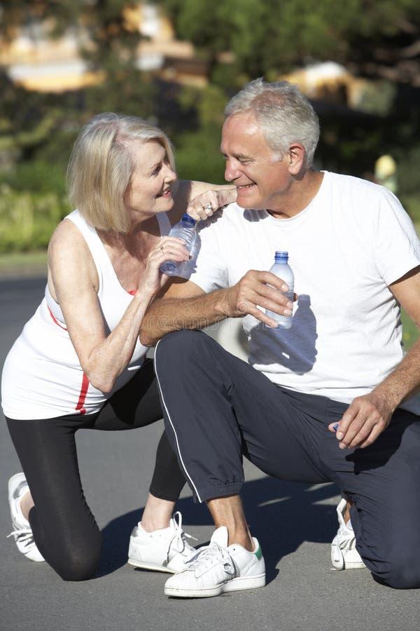 Στηργμένος και πόσιμο νερό ανώτερου ζεύγους μετά από την άσκηση στοκ φωτογραφία