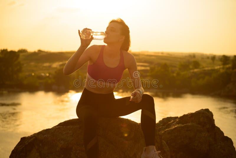 Στηργμένος και πόσιμο νερό γυναικών μετά από να τρέξει υπαίθριο Workout στο καυτό θερινό ηλιοβασίλεμα Αθλητισμός και υγιές ενεργό στοκ φωτογραφίες με δικαίωμα ελεύθερης χρήσης