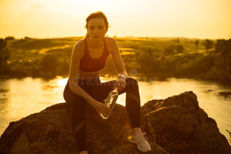Στηργμένος και πόσιμο νερό γυναικών μετά από να τρέξει υπαίθριο Workout στο καυτό θερινό ηλιοβασίλεμα Αθλητισμός και υγιές ενεργό στοκ εικόνα