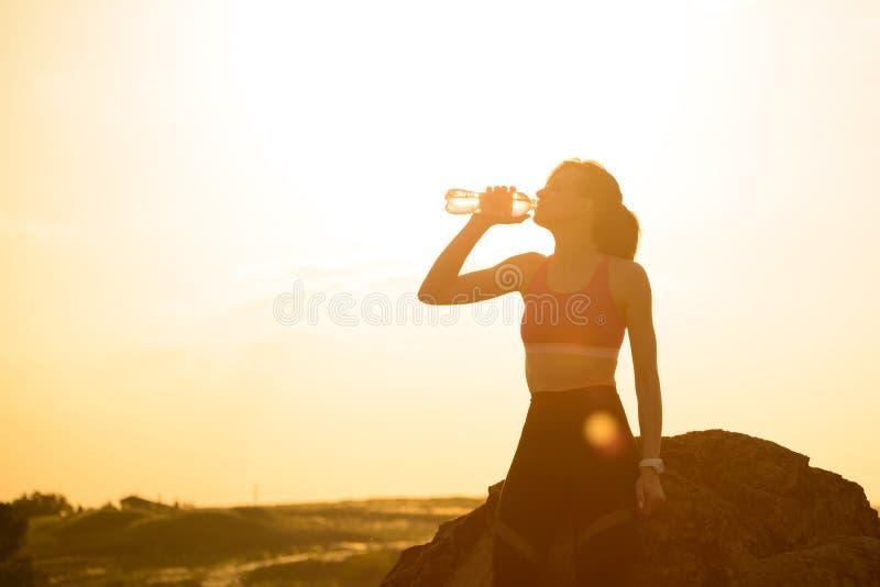 Στηργμένος και πόσιμο νερό γυναικών μετά από να τρέξει υπαίθριο Workout στο καυτό θερινό ηλιοβασίλεμα Αθλητισμός και υγιές ενεργό στοκ φωτογραφία με δικαίωμα ελεύθερης χρήσης