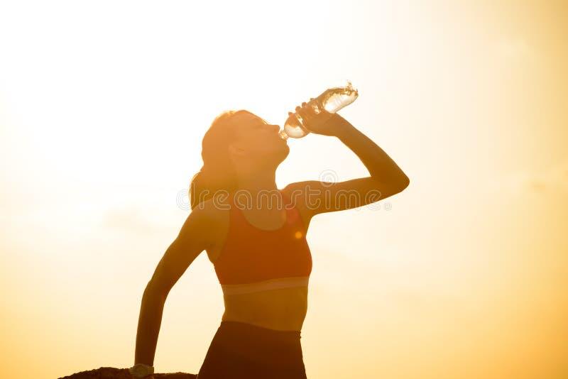 Στηργμένος και πόσιμο νερό γυναικών μετά από να τρέξει υπαίθριο Workout στο καυτό θερινό ηλιοβασίλεμα Αθλητισμός και υγιές ενεργό στοκ εικόνες