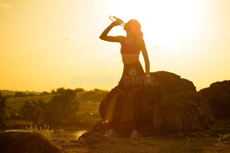 Στηργμένος και πόσιμο νερό γυναικών μετά από να τρέξει υπαίθριο Workout στο καυτό θερινό ηλιοβασίλεμα Αθλητισμός και υγιές ενεργό στοκ εικόνες με δικαίωμα ελεύθερης χρήσης