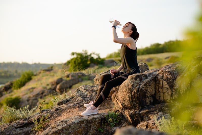 Στηργμένος και πόσιμο νερό γυναικών μετά από να τρέξει υπαίθριο Workout στο καυτό θερινό ηλιοβασίλεμα Αθλητισμός και υγιές ενεργό στοκ φωτογραφία