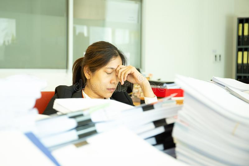 Στηργμένος χέρι επιχειρηματιών στα επικεφαλής μάτια κοντά με το σωρό της γραφικής εργασίας στοκ φωτογραφία