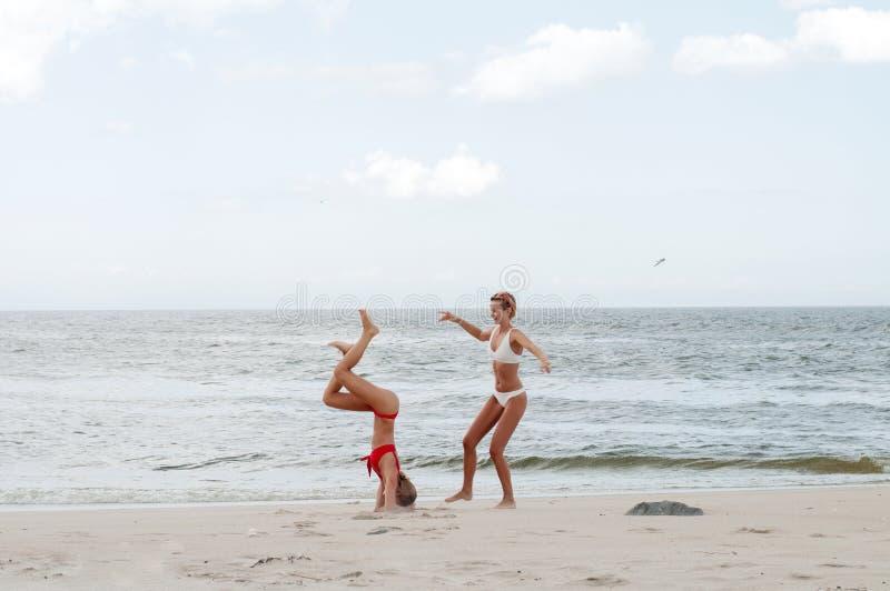 στιγμή ευτυχίας Δύο ελκυστικές γυναίκες στο μπικίνι στην παραλία στοκ φωτογραφίες