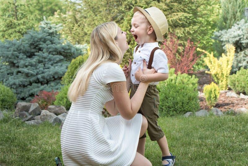 Στιγμή ζωής της ευτυχούς οικογένειας! Παιδί μητέρων και γιων που παίζει έχοντας τη διασκέδαση μαζί στη χλόη στην ηλιόλουστη θεριν στοκ εικόνες