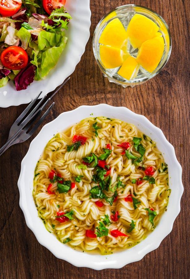 Στιγμιαία νουντλς σε λευκό μπολ σε ξύλινο τραπέζι και σαλάτα λαχανικών στοκ εικόνες