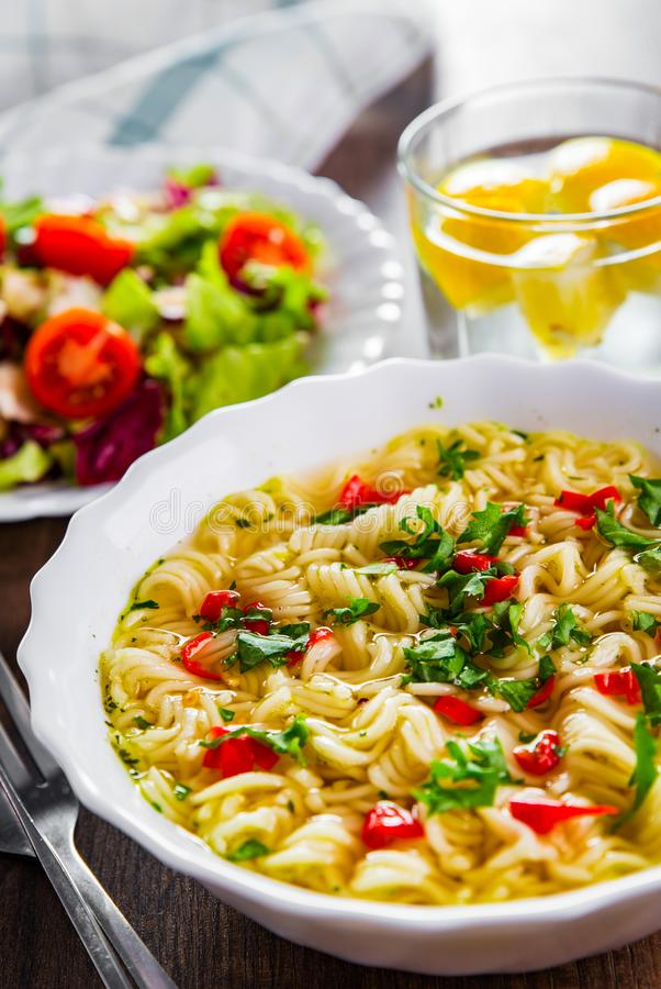 Στιγμιαία νουντλς σε λευκό μπολ σε ξύλινο τραπέζι και σαλάτα λαχανικών στοκ φωτογραφίες με δικαίωμα ελεύθερης χρήσης