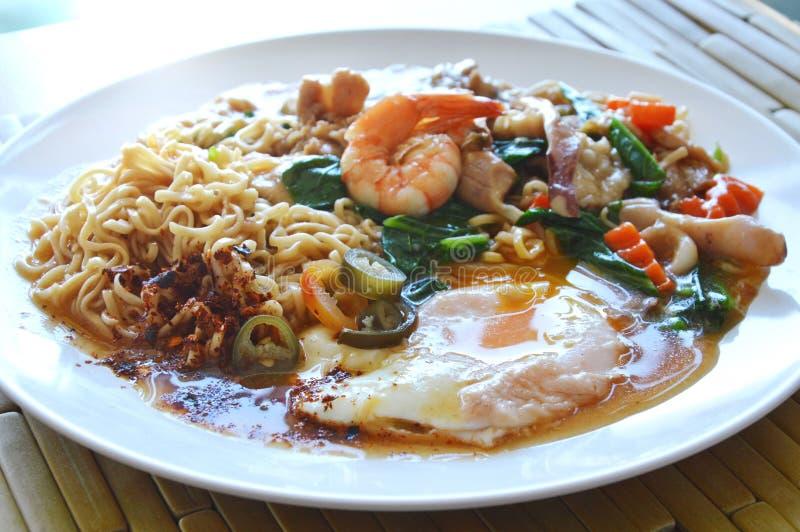 Στιγμιαία σάλτσα ζωμού θαλασσινών επιδέσμου νουντλς και κρεμώδης λέκιθος αυγών στο πιάτο στοκ εικόνες