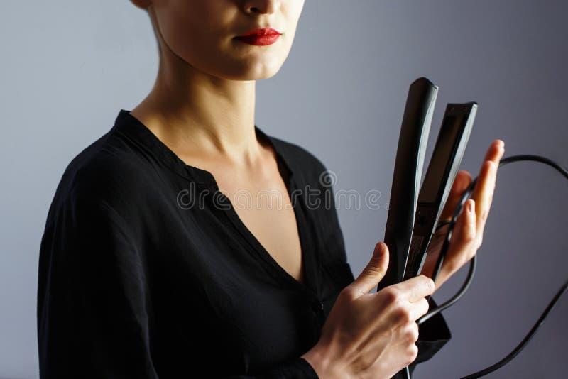 Στιλίστας κοριτσιών που κρατά έναν κατσαρώνοντας σίδηρο για την τρίχα στοκ φωτογραφία με δικαίωμα ελεύθερης χρήσης