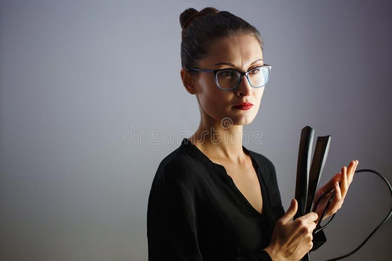 Στιλίστας κοριτσιών που κρατά έναν κατσαρώνοντας σίδηρο για την τρίχα Γκρίζο απομονωμένο υπόβαθρο r στοκ εικόνες με δικαίωμα ελεύθερης χρήσης