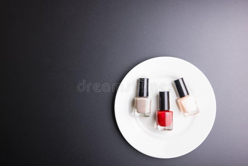 Στιλβωτής καρφιών στο άσπρο πιάτο στο μαύρο υπόβαθρο, έννοια καλλυντικών, έννοια Makeup, διαστημική εικόνα αντιγράφων για το κείμ στοκ εικόνα με δικαίωμα ελεύθερης χρήσης