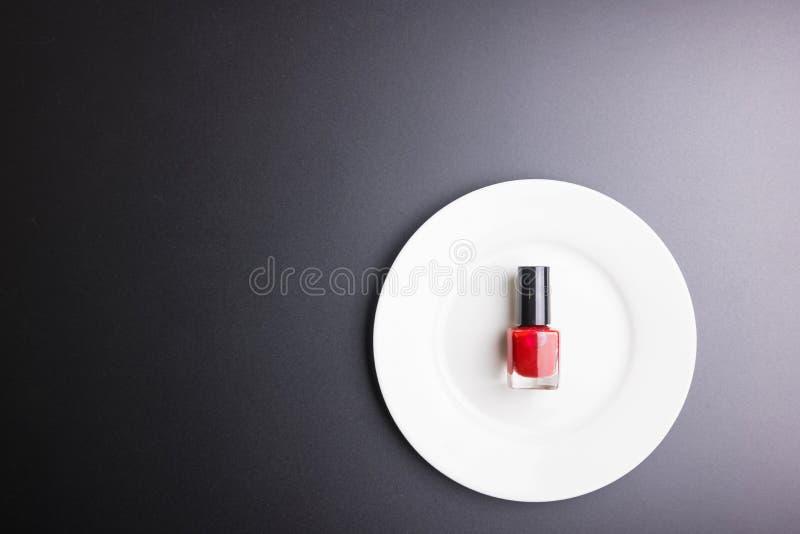 Στιλβωτής καρφιών στο άσπρο πιάτο στο μαύρο υπόβαθρο, έννοια καλλυντικών, έννοια Makeup, διαστημική εικόνα αντιγράφων για το κείμ στοκ εικόνες