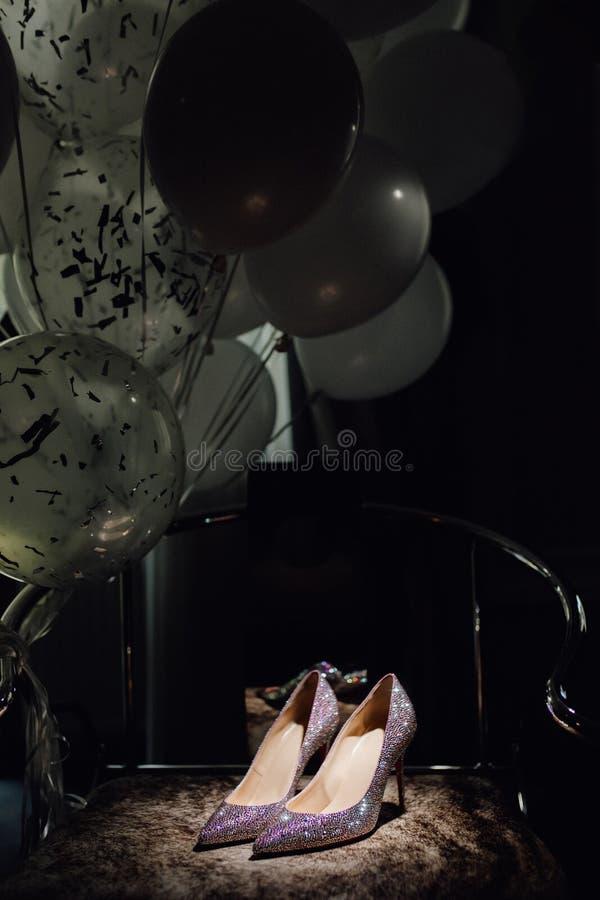 Στιλπνά παπούτσια νυφών στην έδρα και τη φωτογραφία μπαλονιών στοκ φωτογραφία