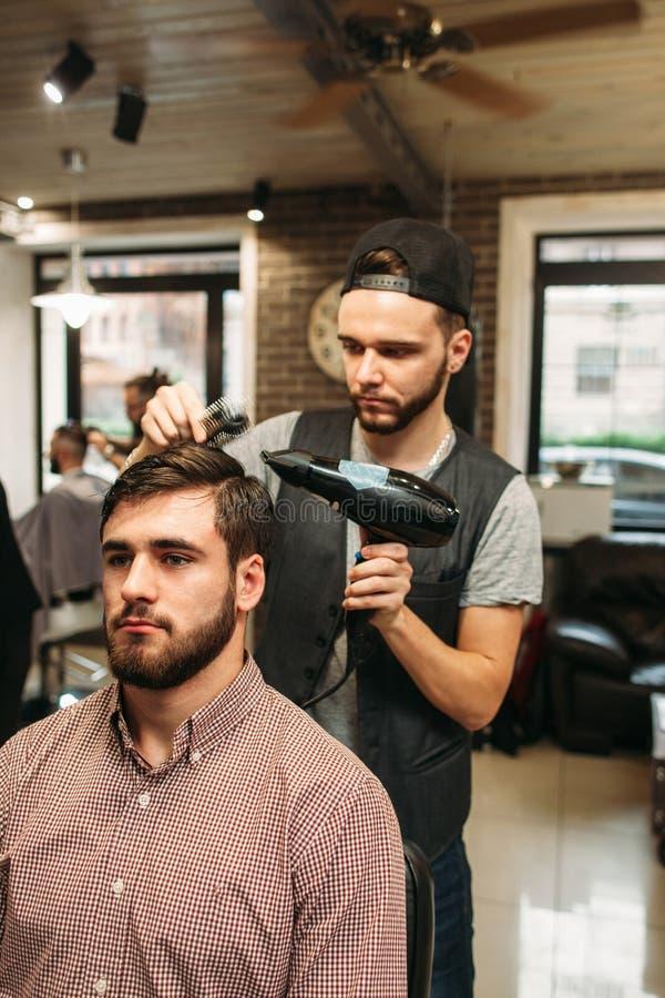 Στιλίστας που κάνει το σύγχρονο hairdo για το νεαρό άνδρα στοκ φωτογραφίες με δικαίωμα ελεύθερης χρήσης
