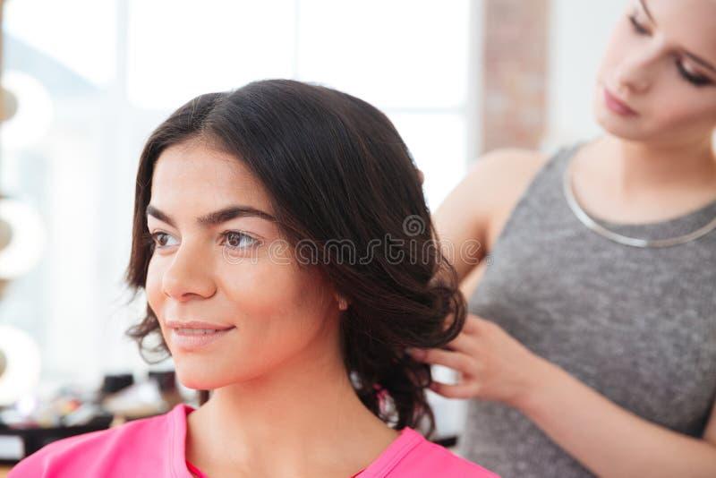 Στιλίστας τρίχας γυναικών που κάνει hairstyle στο νέο θηλυκό πρότυπο στοκ εικόνες