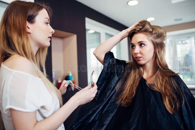 Στιλίστας τρίχας που εργάζεται στα θηλυκά σκέλη ψαλιδίσματος hairdo πελατών s με τις καρφίτσες τρίχας hairdressing στο στούντιο στοκ εικόνες με δικαίωμα ελεύθερης χρήσης