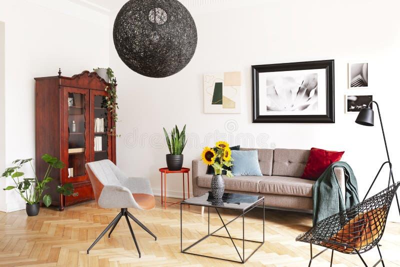 Στοά των εικόνων σε έναν άσπρο τοίχο επάνω από έναν άνετο καναπέ με τα ζωηρόχρωμα μαξιλάρια σε ένα μοντέρνο εσωτερικό καθιστικών  στοκ εικόνα με δικαίωμα ελεύθερης χρήσης