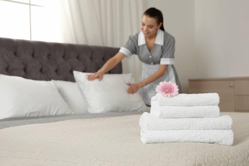 Στοίβα από καθαρές πετσέτες με λουλούδι στο κρεβάτι και θολή καμαριέρα στο δωμάτιο του ξενοδοχείου Χώρος για κείμενο στοκ εικόνες
