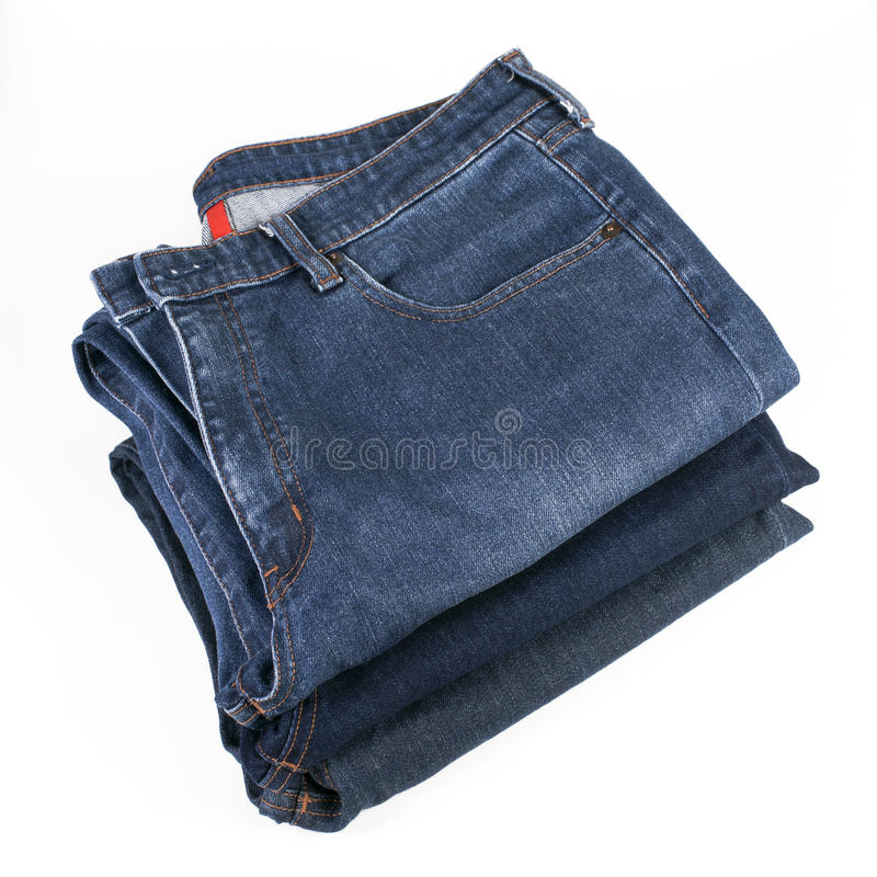 Στοίβα του διπλωμένου τζιν παντελόνι σε μια άσπρη ανασκόπηση στοκ εικόνες