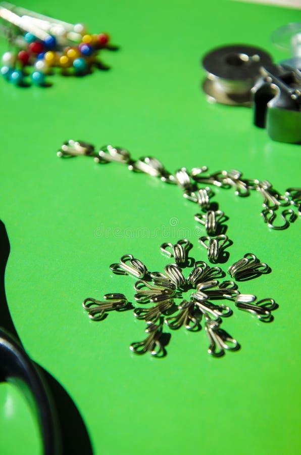 Στοιχεία μόδας: γάντζος μετάλλων και ιδιαίτερες προσοχές σε ένα πράσινο υπόβαθρο στοκ εικόνα